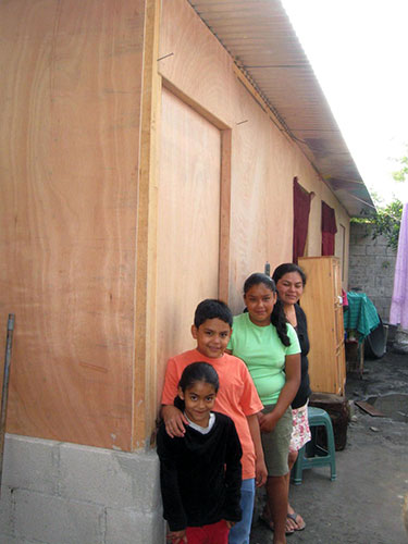 Eber (8) with his family in front of their new room addition.